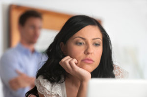 Upset woman looking at a computer screen with man in background